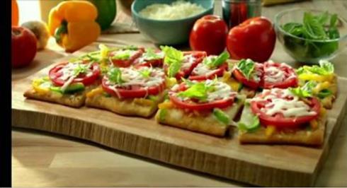 Плоский хлеб с томатами и зеленым перцем, а также оливковым маслом, чесноком и сыром моцарелла.